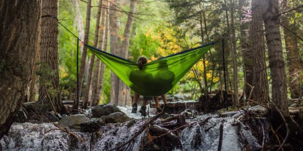 A couple sits in a green hammock over a stream in the forest.