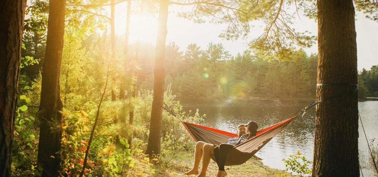 A couple share a smile together as they sit in a hammock between two trees at the edge of a sunlit lake.