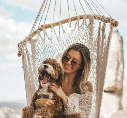 Young woman sits in a Brazillian hammock chair holding her dog