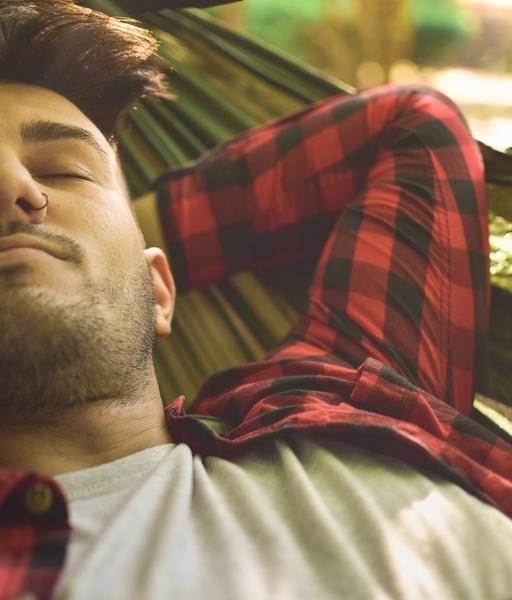 Man wearing red and black plaid shirt sleeps in a green camping hammock