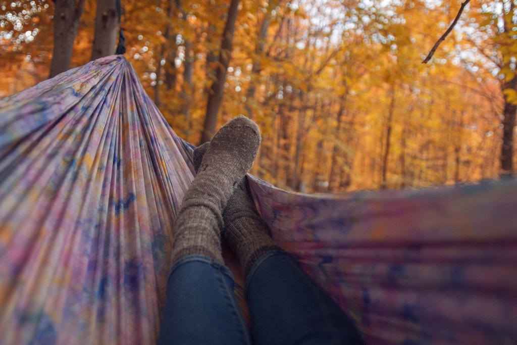 Woman lies in a pink hammock wearing grey wool socks
