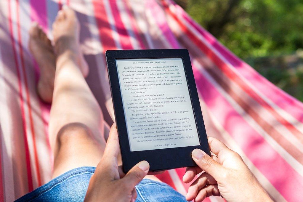 Pesona leyendo un e-book en su hamaca rosa y amarilla