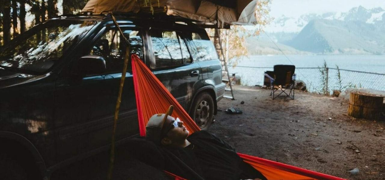 Man hangs on hammock at camping ground with his hammock tied to a tree and his vehicle